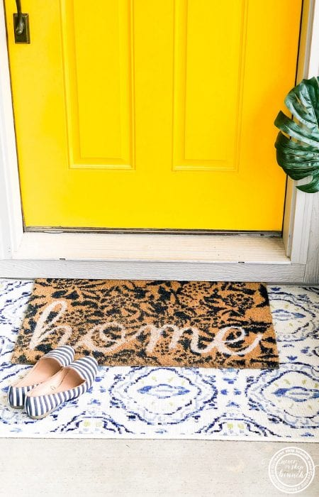 layered rugs at yellow front door